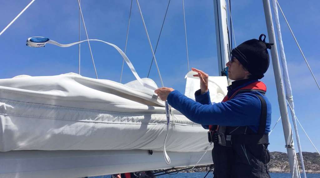 Caroline throwing the weighted sail tie over the sail